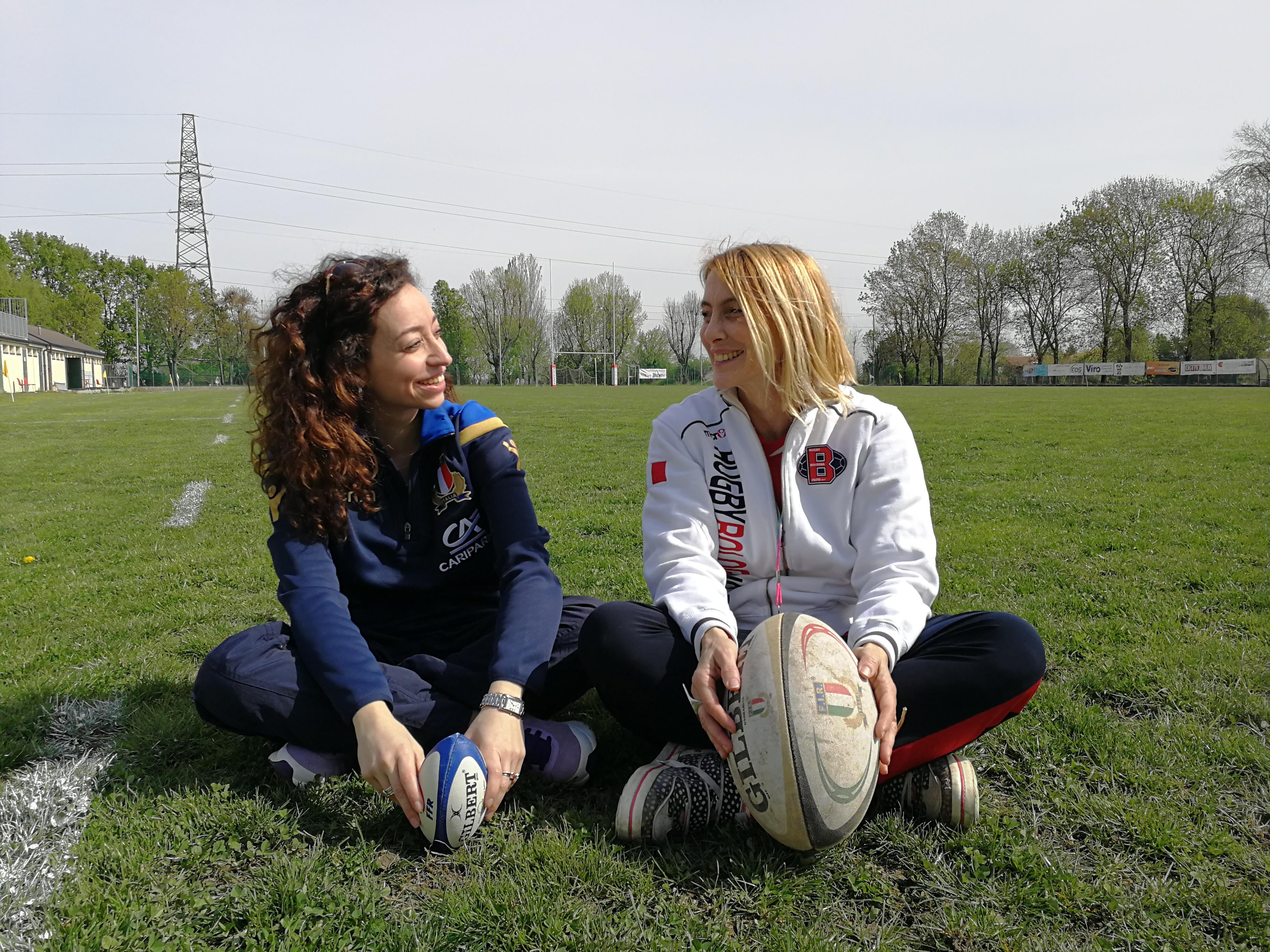 Elisabetta ed Erika sedute sull'erba con un pallone da rugby
