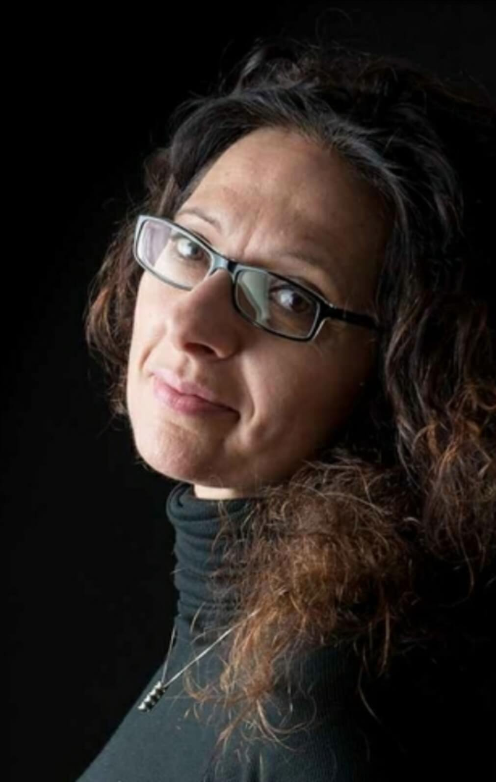 Maria Chiara è castana, con capelli lunghi e occhiali