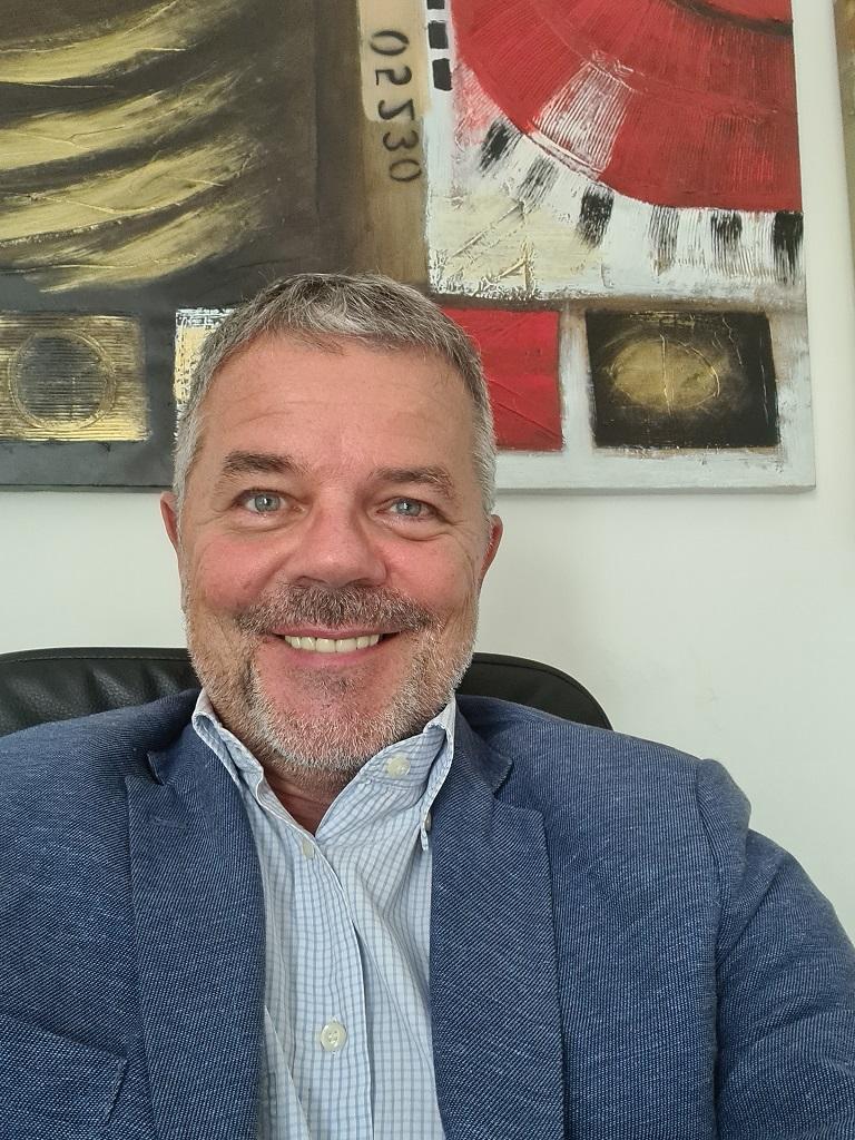 Fabio è castano, con capelli brizzolati e occhi scuri, barba a media lunghezza, nella foto sorride seduto alla sua scrivania