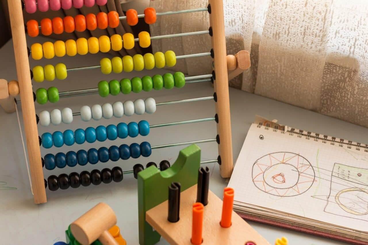 Un pallottoliere, un quaderno con dei disegni a pastello e altri giochi posti in un interno, vicino la finestra.