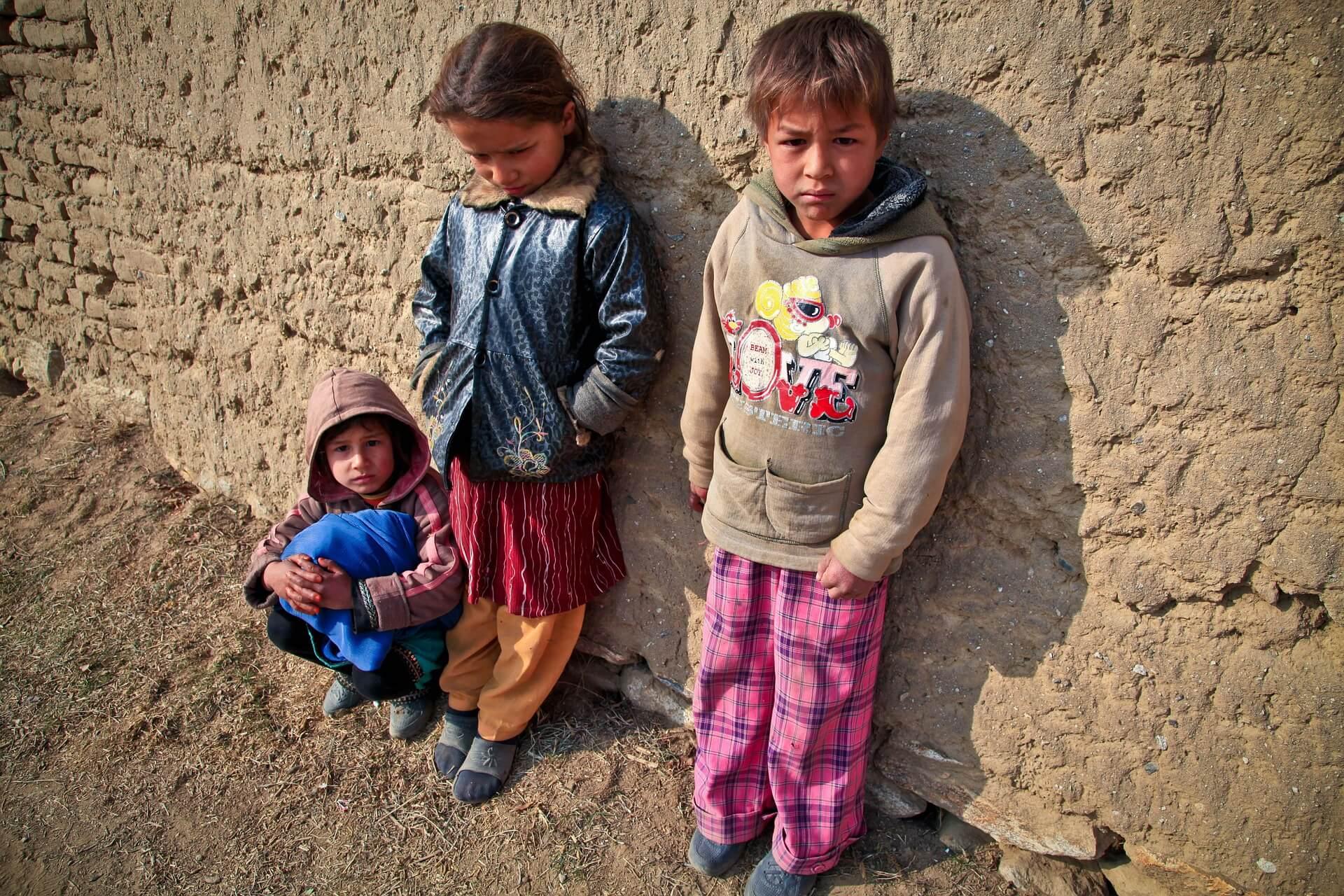 tre bambini siriani con abiti sporchi appoggiati ad un muro di pietra