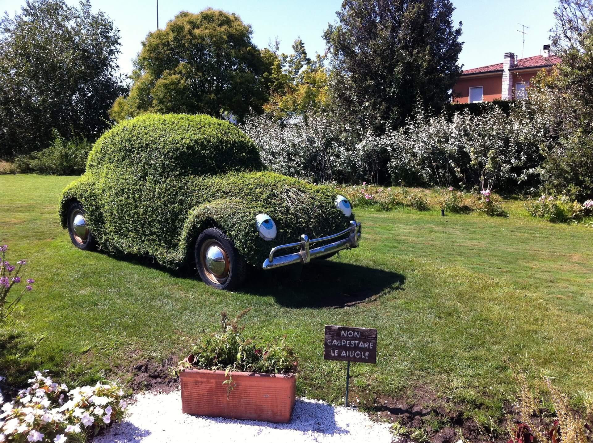macchina di tipologia maggiolone ricoperta di erba e parcheggiata in un cortile