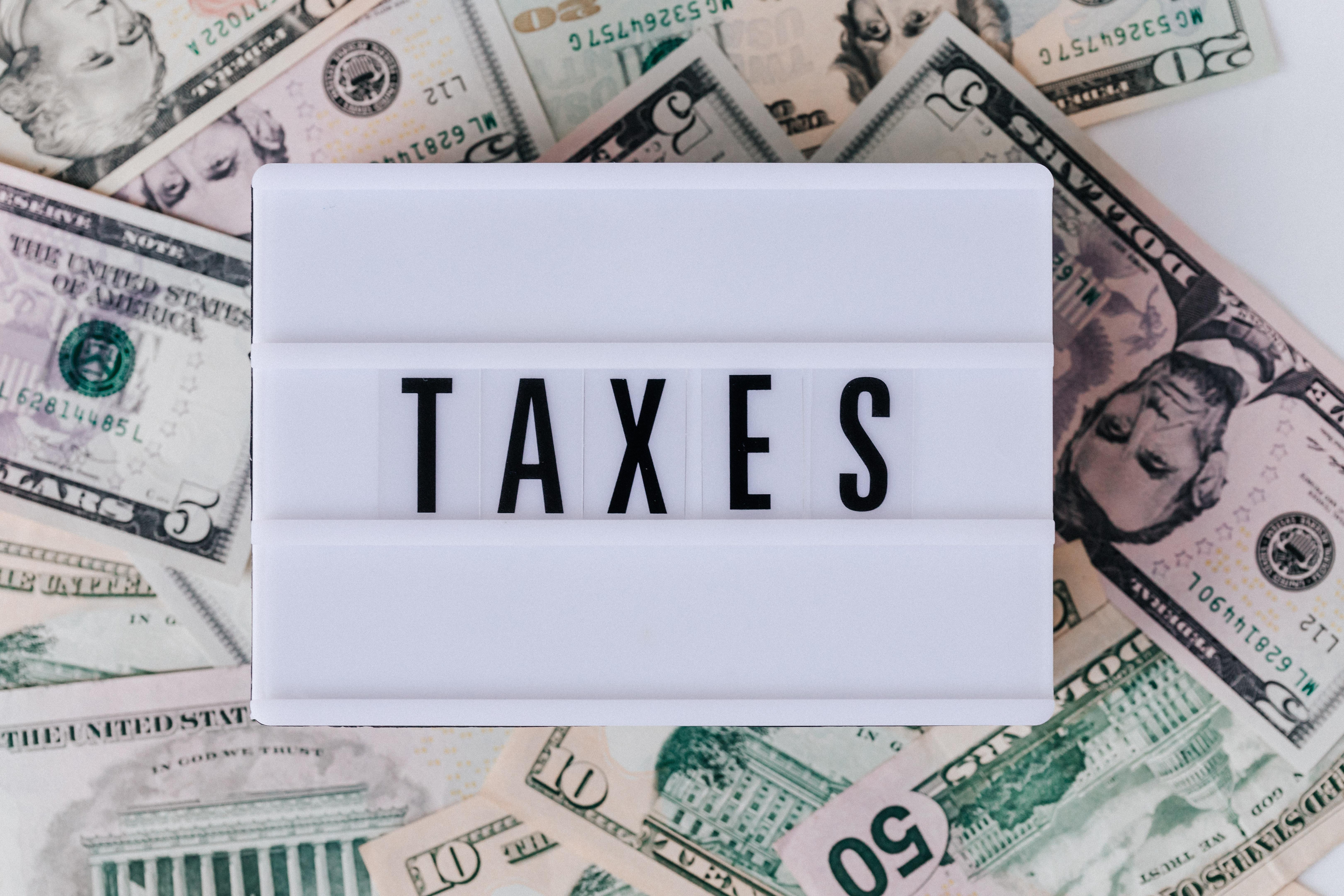 """dfoto di varie banconote con sopra appoggiata la scritta """"TAXES"""""""