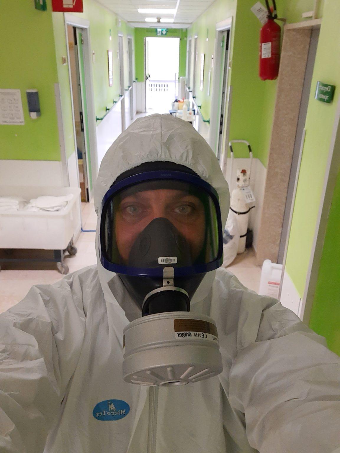 Un uomo con una tuta tyvek e una maschera con filtro assoluto all'interno di una corsia ospedaliera